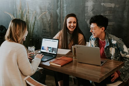 Three multicultural women laugh as they study together at a table with two open laptops.