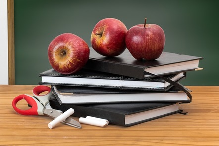 Books, apples, chalk and scissors rest on a wooden table in from of a blackboard