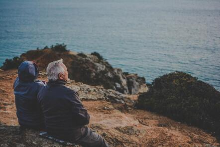An older man and wife sit on a bench on a cliffside facing the Atlantic Ocean.
