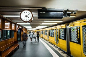 A station platform on a German underground railway, with a clock and train indicator board and several passengers walking beside a bright yellow train.