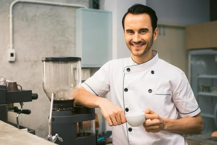 Man in chef uniform holding coffee cup by coffee machine