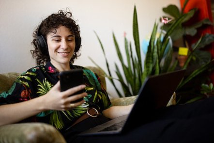 Nonbinary person smiles as they complete some online learning, holding their laptop on their lap and their phone in their right hand.
