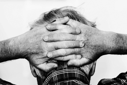 Old man with hands behind his head