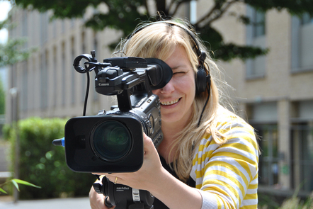 A young woman using a film camera outside. Her focus is down the lens of the camera and she wears headphones.