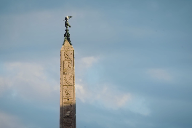 A photo of an obelisk that has a bird sitting on the top