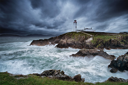 A view of a coastal lighthouse in Ireland in turbulent weather.