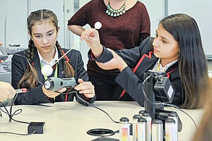 Teaching Secondary Science: young girls using science technology in a classroom as a teacher observes