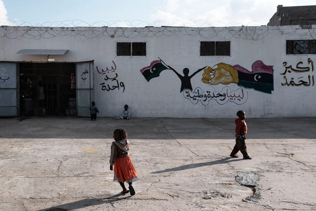 A very young girl in a bright orange skirt and a very young boy in a red shirt are outside a building with wire on the roof and graffiti on the white cement wall. The graphic is arabic writing with a silhouette of a person holding flags.