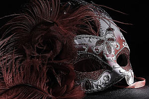 A feather and glitter decorated mask
