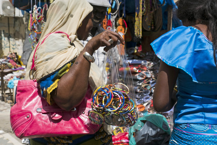 A woman holds a bag of bracelets at the Malian market in the Plateau district of Dakar, Senegal.