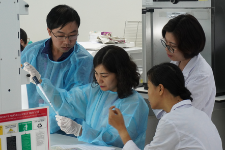 learner in the lab pippeting and others watching