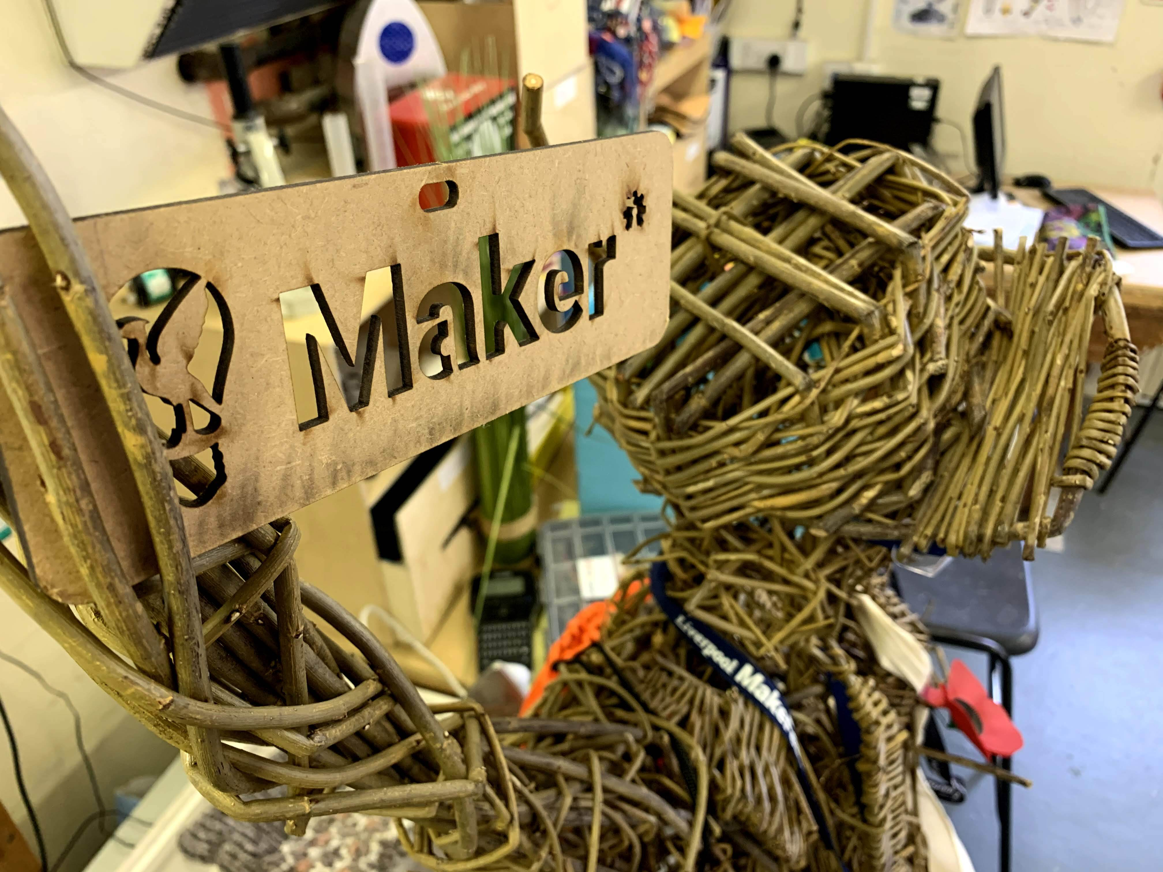 A wicker model of a person with a maker sign