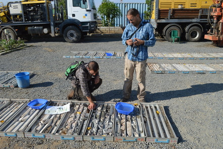 2 geologists look at core samples laid out on the ground side by side.