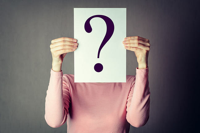 Portrait of casual anonymous woman covering face with paper showing question mark