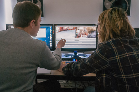 two students at a screen editing
