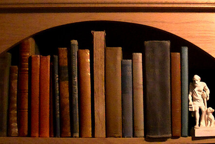 A photograph of a row of books on a bookshelf with a white statue at the end of a Greek philosopher