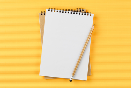 A picture of a notebook and pen on a yellow desk.