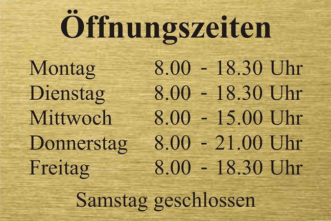 A sign showing opening times. It reads: Öffnungszeiten. Montag 8.00 - 18.30 Uhr. Dienstag 8.00 - 18.30 Uhr. Mittwoch 8.00 - 15.00 Uhr. Donnerstag 8.00 - 21.00 Uhr. Freitag 8.00 - 18.30 Uhr. Samstag geschlossen.