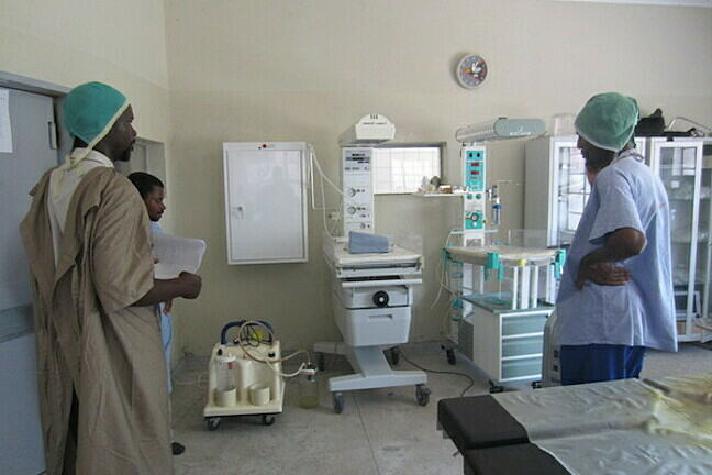 Image of 3 clinical staff in a ward looking at equipment which is for viewing X-rays on a light box, two baby monitor beds to provide light to babies, equipment cupboards with glass doors and medical bed behind them.