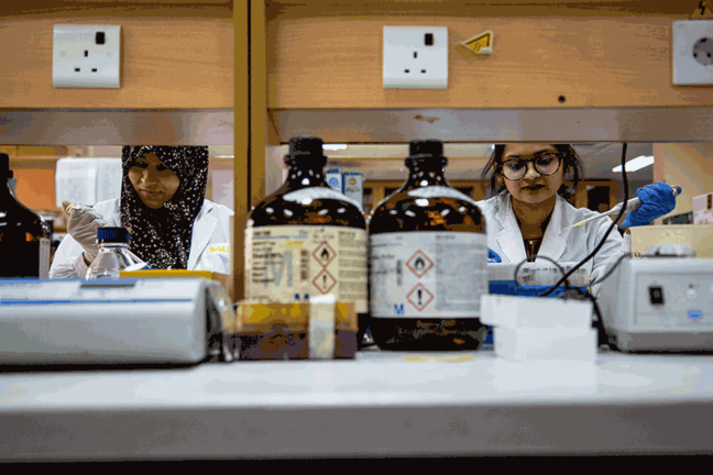 Two women wearing laboratory coats and gloves are standing behind a table with two big amber bottles and laboratory equipment. They are each holding a pipette to test samples for pathogens.