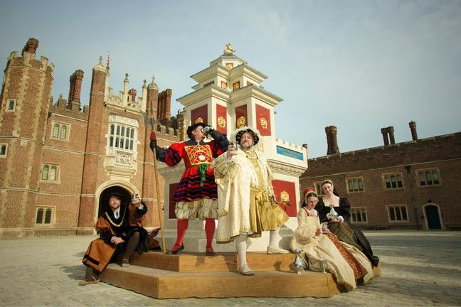 A photograph of a reenactment at Hampton Court Palace. Henry VIII is posing by a monument with 4 courtiers around him.