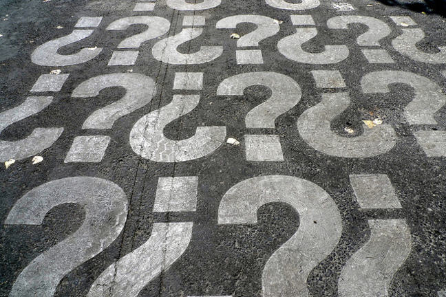 White question marks printed on black tarmac
