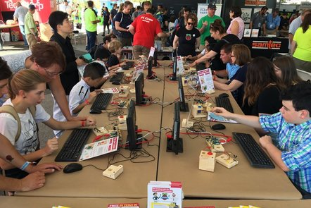 People engaged in digital making activities at a faire