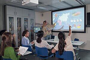 A teacher shows data visualiations to a classroom of students