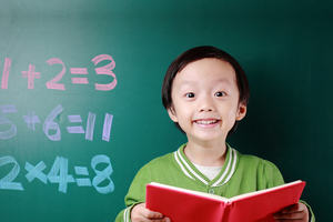 A child holds an open book in front of a blackboard