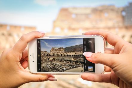 Hands holding a smartphone, taking a photo of a historical site