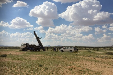 Drilling at Eureka in Namibia. A flat landscape with a lorry-mounted drill and a 4x4 vehicle.