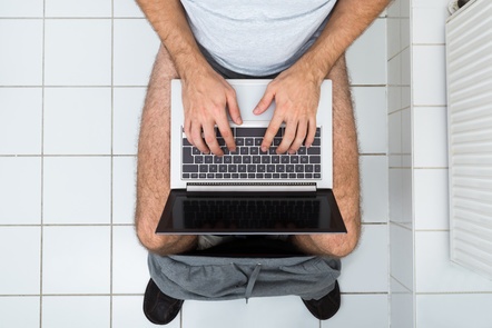 High angle view of a man in toilet using a laptop computer. Image by AndreyPopov / Pond5