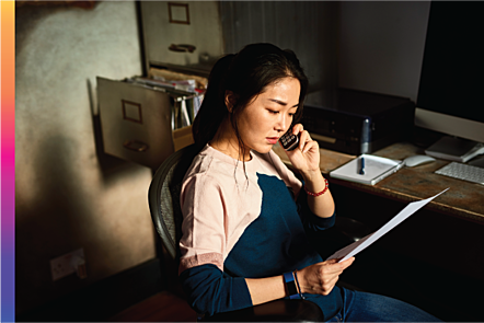 Photographic image of a woman sitting at an office desk talking on the phone while reading from a piece of paper