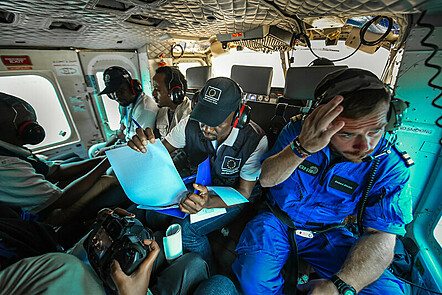 Six humanitarian workers seated in helicopter monitoring aid programmes.