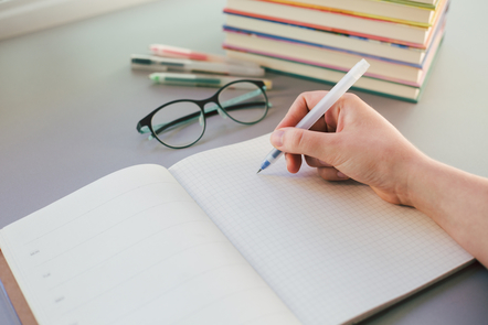 A hand writes on a bullet journal at a desk with a pair of glasses and a stack of books.