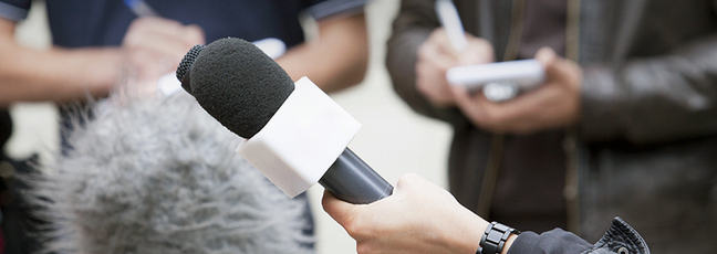 A man being interviewed with microphones in the foreground and people taking notes in the background.