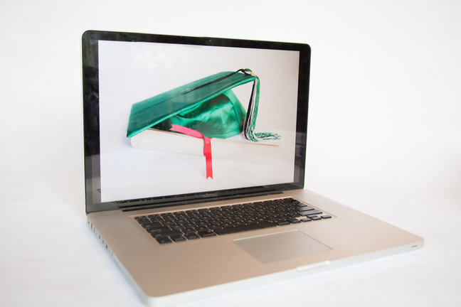MAC laptop which has an image on screen. The image is a graduates mortar on a book.