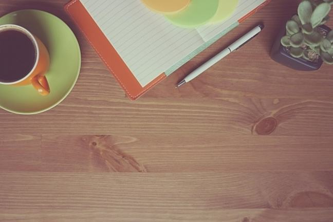 Cup of coffee, notebook, pen, and plant on a desk