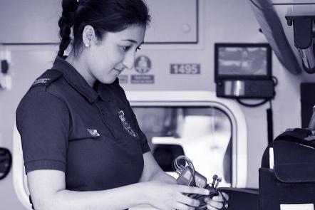 Paramedic checking equipment in ambulance