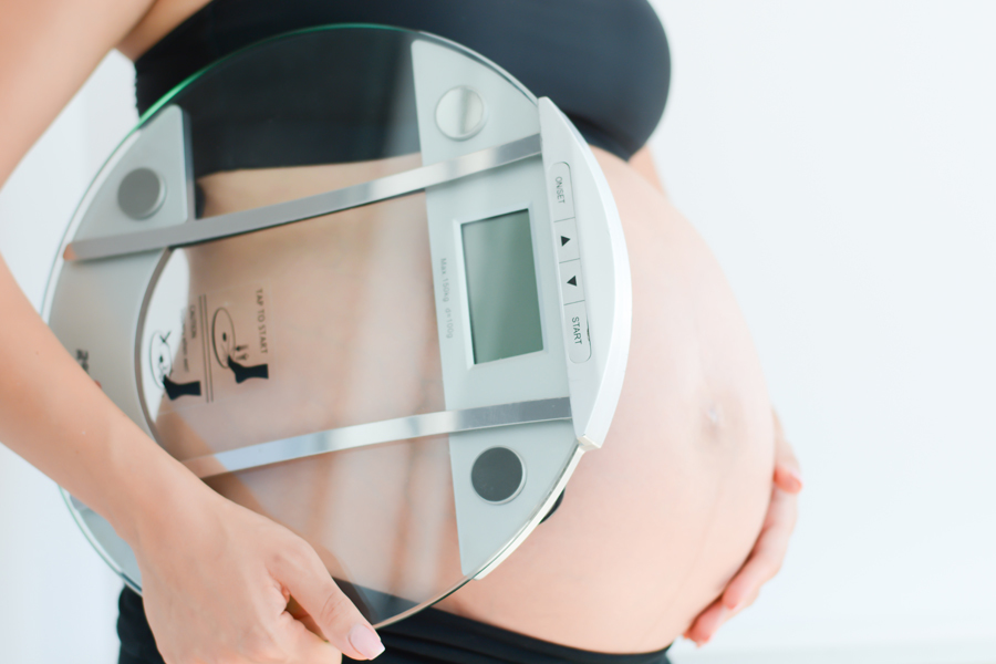 Weight gain during pregnancy with pregnant woman holding scale.