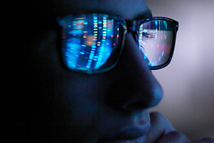 Close-up of a man's face who's glasses are reflecting a computer screen.