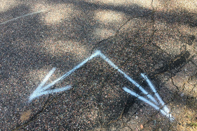 Blue arrows on tarmac marking two directions