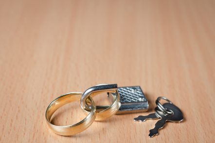 Photo of two gold wedding rings with padlock and key