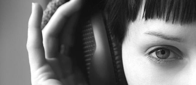 A close up shot of a woman wearing headphones.