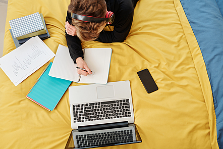 An overhead view of a student studying. They're writing in a notebook, with a laptop in front of them, and have headphones on.