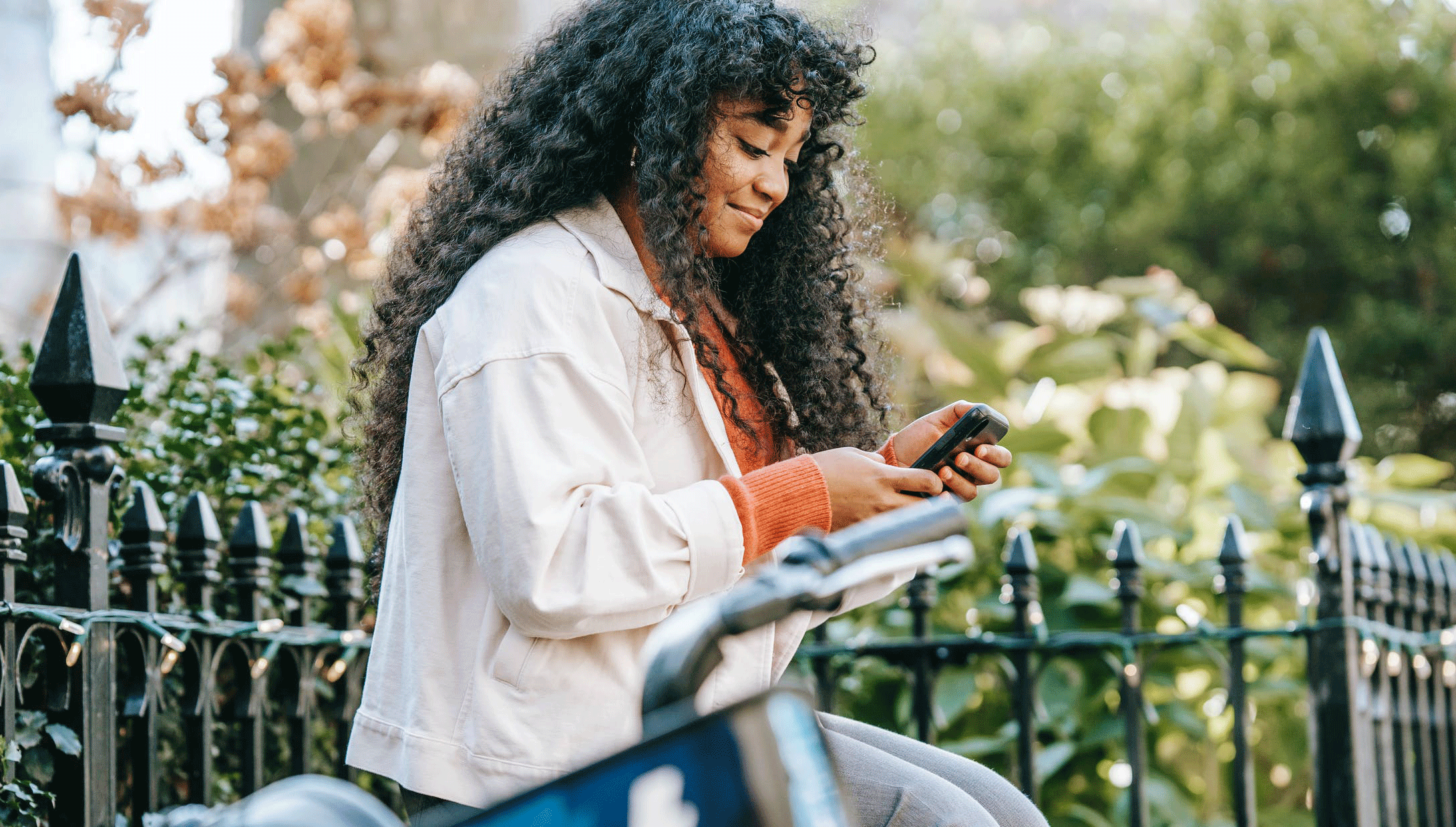 Woman with smartphone sitting on a bench near a bike by a park gate.