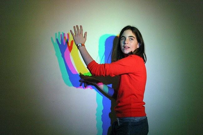 Woman stood in front of a white wall with a multicoloured shadow.