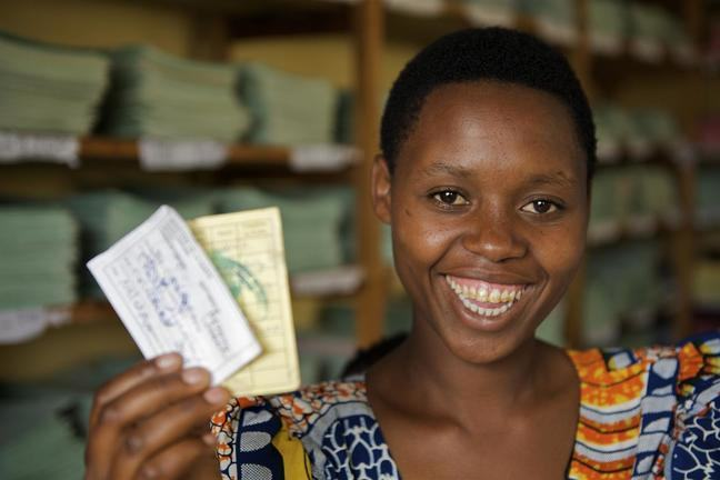 An African woman is shown smiling as she proudly holds insurance cards in her right hand.