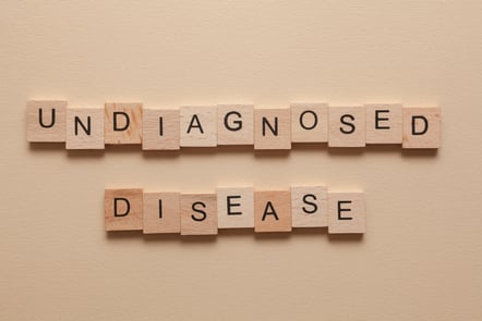 """The words """"undiagnosed"""" and """"disease"""" in wooden letters on a brown background."""
