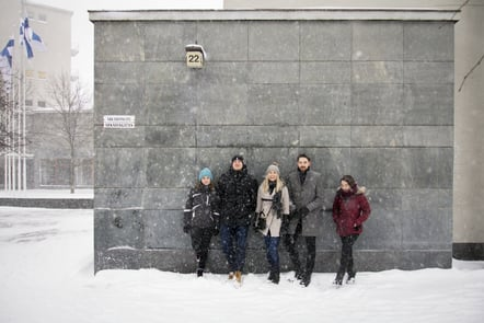 Five students standing against the wall of their school in snowy weather smiling